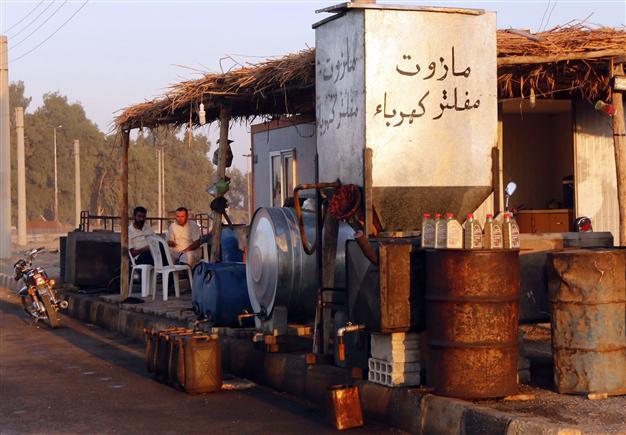 Zwei Verkäufer in der IS-Hochburg Raqqa verkaufen am Straßenrand Benzin und Diesel. Das IS-Gebiet ist durchzogen von Kleinstraffinerien und –verkäufen wie diesem. Reuters, via Hürriyet Daily News