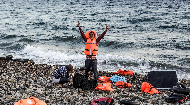 Ein syrischer Flüchtling zeigt das Victory-Zeichen, nachdem sein Schlauchboot von der Türkei kommend heil an der griechischen Insel Lesbos angekommen ist. By Freedom Hous, flickr, published under public domain (edited).