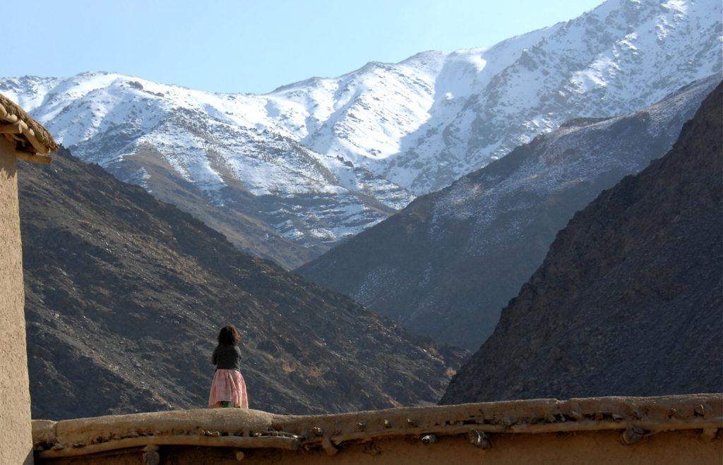 Ein Mädchen schaut auf die schneebedeckten Berge im afghanischen Shinwari District. By Afghanistan Matters, licensed under CC BY 2.0.